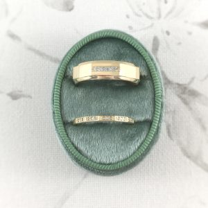 wide and thin geometric diamond wedding bands in green ring box