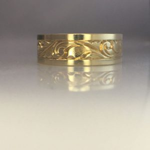 Scrolls and French curves ardorn the surface of a wide, men's yellow gold wedding band. Engraved into the surface.